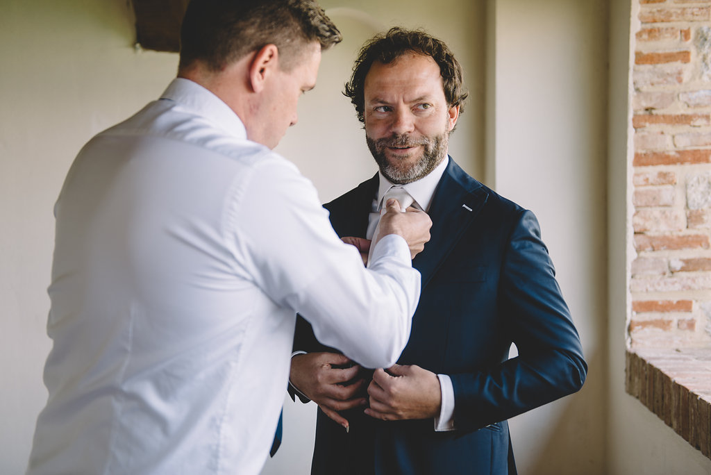 Groom is getting ready, destination wedding in Tuscan Castle di Montalto