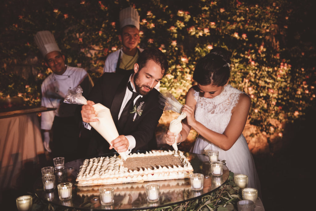 Wedding couple doing wedding cake- Wedding at Castello di Meleto - Italian Wedding Designer